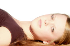 Pretty teenager. Eighteen year old girl laying on her back with white background Royalty Free Stock Photos