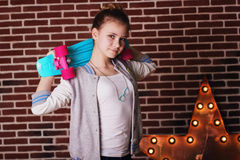 Pretty teenager girl with blue skateboard Stock Photos