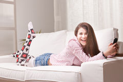 Pretty teenager girl checking her mobile phone. Pretty smiling teenager girl checking her mobile phone Royalty Free Stock Images