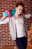 Pretty teenager girl is holding blue skateboard Royalty Free Stock Photo