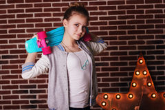 Pretty teenager girl is holding blue skateboard Stock Image