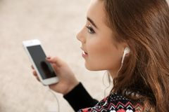 Pretty teenager girl with phone sitting in   room. Pretty teenager girl with phone sitting in living room Royalty Free Stock Images