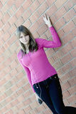 Pretty teenager girl in pink shirt and jeans. Standing next to a brick wall Royalty Free Stock Images