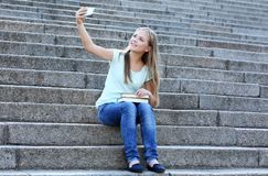 Pretty teenager girl taking selfie while sitting on stairs Stock Images
