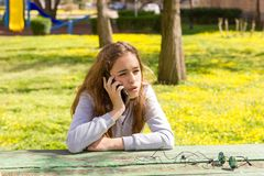Pretty teenager girl talking by mobile cellpfone smartphone at the summer park stock photos