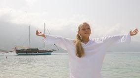 Pretty teenager girl in white tunic with raised hands on sea and ship landscape. Traveling girl enjoying sea beach on stock video footage