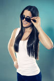 Pretty teenager looking over her sunglasses Royalty Free Stock Photography