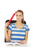 Pretty teenager woman holding huge pencil. Royalty Free Stock Photography
