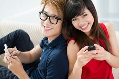Pretty teens. Portrait of attractive teens with cell phones Royalty Free Stock Photography