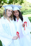 Pretty Teens at Graduation. Pretty young women at graduation with their diplomas Stock Photo