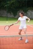 Pretty tennis player hitting ball Stock Photography