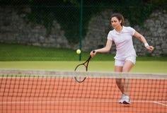 Pretty tennis player hitting ball Stock Photo