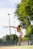 Pretty tennis player hitting ball Royalty Free Stock Photos