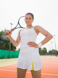Pretty tennis player holding racket smiling at camera Stock Images