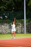 Pretty tennis player serving the ball Royalty Free Stock Image