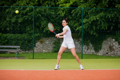 Pretty tennis player about to hit ball Stock Photos