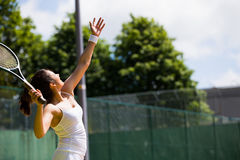 Pretty tennis player about to serve Stock Image