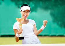 Pretty tennis player won the competition. Pretty tennis player won the cup at the sport competition. Victory Stock Images