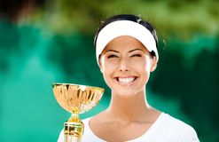 Pretty tennis player won the match. Tennis player won the cup at the sport contest. Trophy Stock Photography