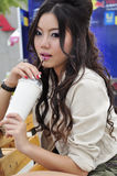 Pretty Thai girl with long hair drinking Stock Images