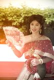 The pretty Thai lady in Middle Thai classical traditional dresses suit pose sitting hold a fan in a park. The smiley face pretty Thai lady in Middle Thai royalty free stock photography