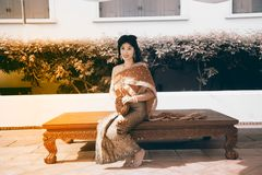 The pretty Thai lady in Middle Thai classical traditional dresses suit pose sitting hold garland in a park. The smiley face pretty Thai lady in Middle Thai stock image