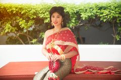 The pretty Thai lady in Middle Thai classical traditional dresses suit pose sitting hold garland in a park. The smiley pretty Thai lady in Middle Thai classical stock photography
