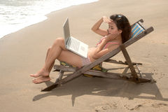 Pretty Thai woman working with laptop on beach bed . Royalty Free Stock Image
