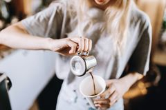 A pretty thin blonde girl with long hair, dressed in casual outfit, pours coffee into a glass in a cozy coffee shop. royalty free stock photo