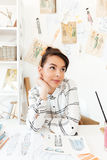 Pretty thinking woman fashion illustrator drawing. Photo of young pretty thinking woman fashion illustrator sitting at the table and drawing. Looking aside stock photos