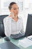 Pretty thoughtful businesswoman sitting at her desk Royalty Free Stock Photo