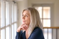 Pretty thoughtful woman with serious expression. Attractive thoughtful woman with serious expression standing with her hand to her chin staring quietly out of a stock photography