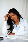 Pretty tired young black female learning Stock Image