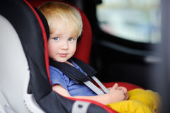Pretty toddler boy sitting in car seat Stock Image