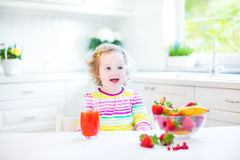 Pretty toddler girl having breakfast drinking juice Royalty Free Stock Photos