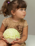 Pretty toddler girl holding cabbage and smiling Stock Image