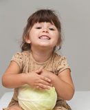 Pretty toddler girl holding cabbage and smiling Royalty Free Stock Photos