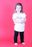 Pretty toddler girl holding her hands. On pink background Royalty Free Stock Photo