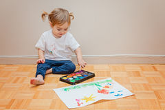 Pretty toddler girl learning how to draw. With watercolor royalty free stock image