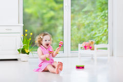Pretty toddler girl playing maracas in white room Royalty Free Stock Images
