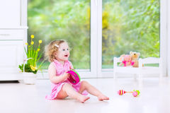 Pretty toddler girl playing tambourine in white room Royalty Free Stock Images
