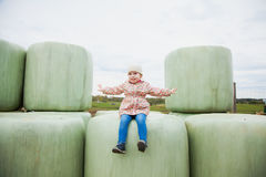 Pretty toddler girl sits on haylage, feel freedom. Rich harvest, Royalty Free Stock Photo
