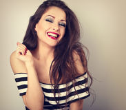 Pretty toothy laughing fun makeup woman with hand near hair on b Stock Image