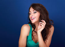 Pretty toothy laughing makeup woman with hand near hair on blue Royalty Free Stock Photo