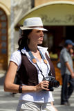 Pretty tourist girl with camera. Standing on the street royalty free stock photo