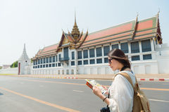 Pretty tourist woman reading travel guidebook. Smiling pretty tourist woman reading travel guidebook standing on grand palace roadside searching information map stock photo