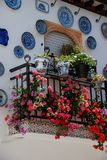 Pretty townhouse balcony, Granada. Wrought iron balcony on a traditional Spanish townhouse with assorted flowers and decorated plates in the Albaicin District Stock Photo