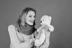 Pretty toy concept. Lady with blond hair hugs cute toy bear. Woman holds teddy bear on red. Girl with happy face stock images