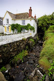 Pretty traditional house by a stream. Pretty traditional white house by a stream - portrait Royalty Free Stock Image