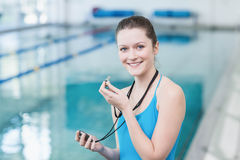 Pretty trainer blowing whistle and looking at stopwatch Stock Photography